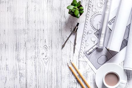 Ett skrivbord med olika linjaler och pennor.
