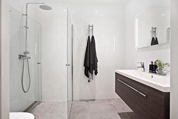 Smakfulla materialval i gråt i ett badrum med badkar.