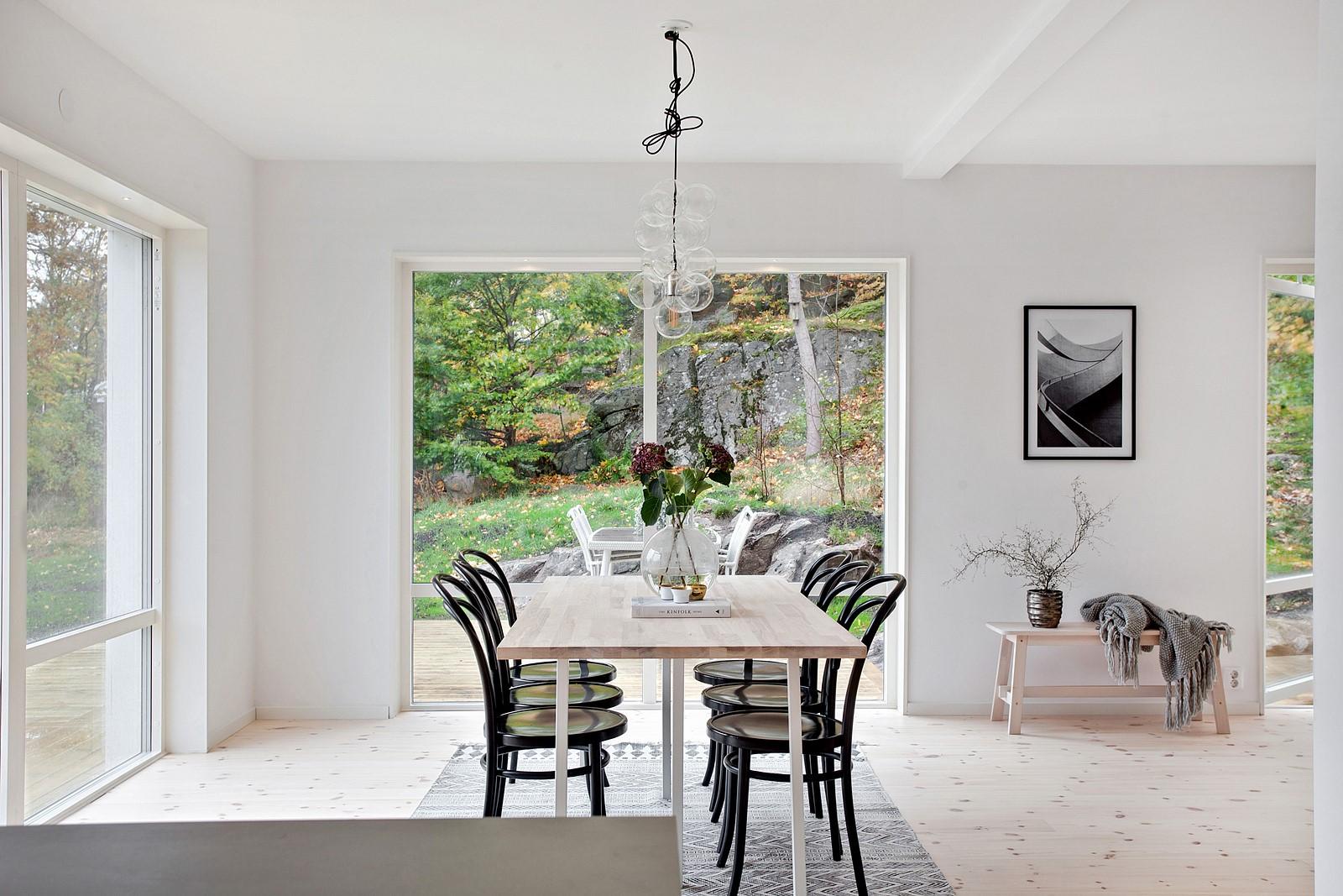 Matplats med bort och stolar för 6 personer.På bordet finns en bukett med blommor.