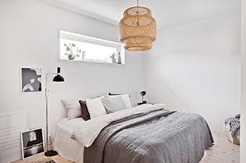 Inspiration för inredning i ett sovrum. I sovrummet finns säng med grått överkast. Tavlor i svart-vitt.