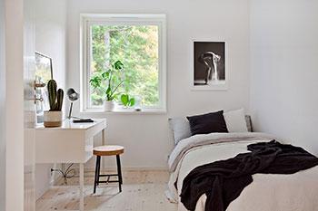 Inredning sovrum för tonåring. Skrivbord i vitt och säng med svart pläd och svart kudda på.