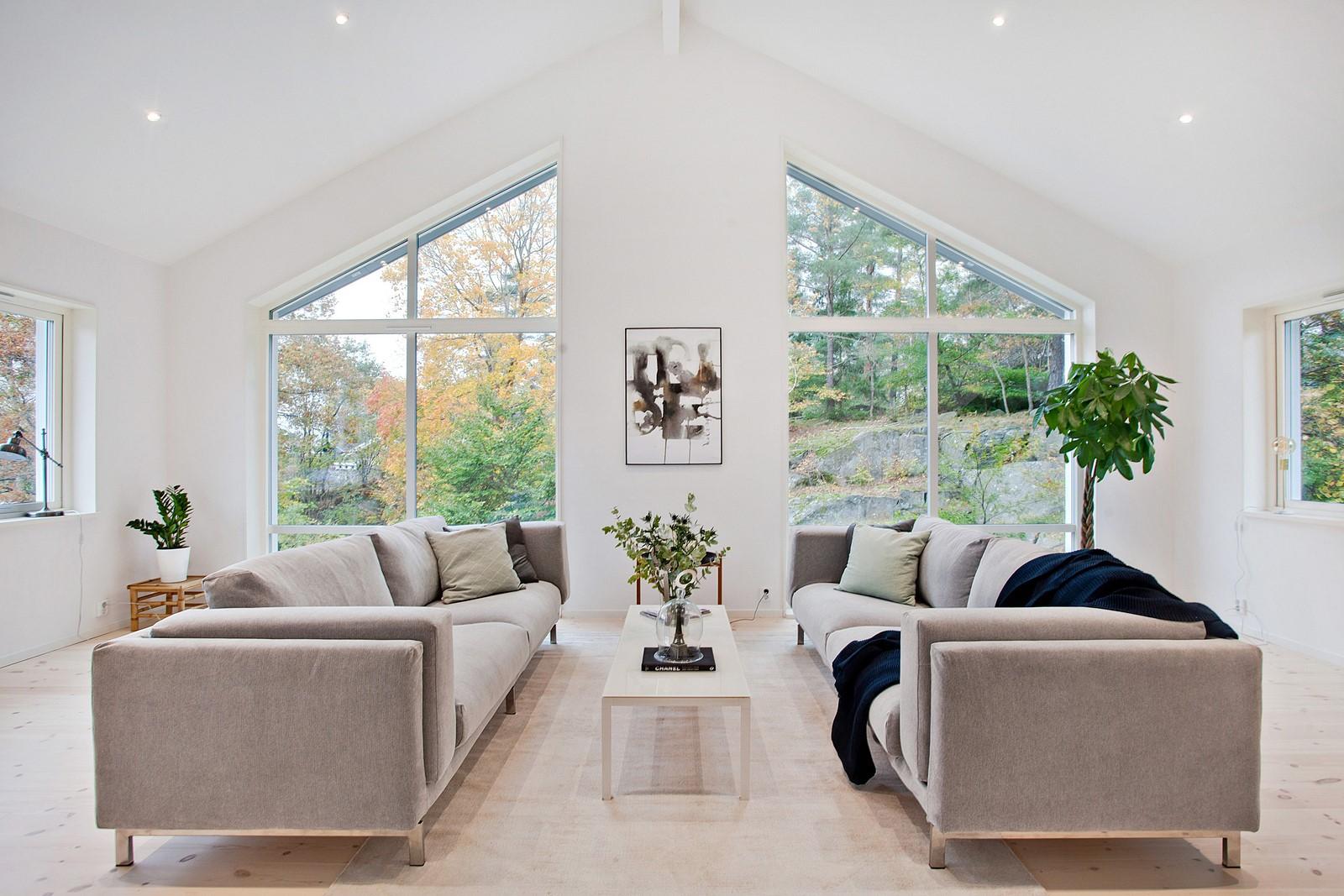 Vardagsrum med två soffor. Stora fönster, högt i tak.
