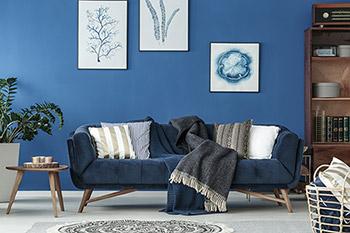 Rum med retrosoffa och bord i teak. Blåa väggar.